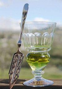 A reservoir glass filled with a naturally coloured verte absinthe, next to an absinthe spoon.