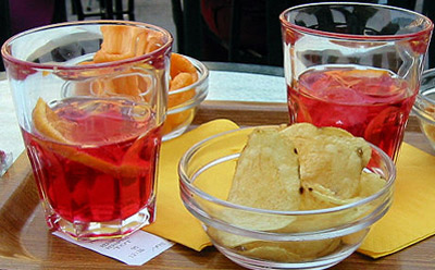 Two glasses of apéritifs (Campari with carbonated water) served with potato crisps and peanuts as appetizers.