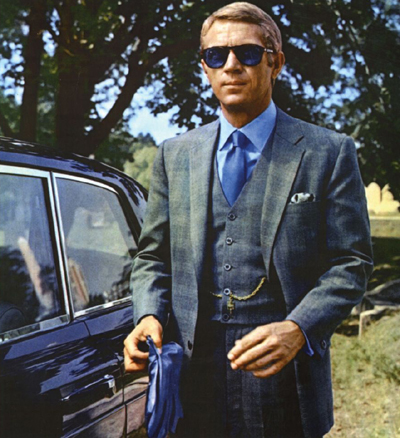 Steve McQueen's legendary first suit worn as Thomas Crown is a medium gray three-piece with a muted Glen Plaid or 'Prince of Wales' check made by Douglas Hayward.