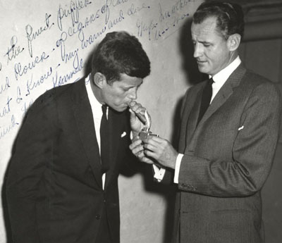 John F. Kennedy lights up cigar with his close friend Senator George Smather of Florida.