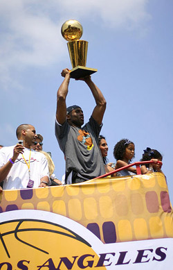 Kobe Bryant holding the Larry O'Brien Championship Trophy.