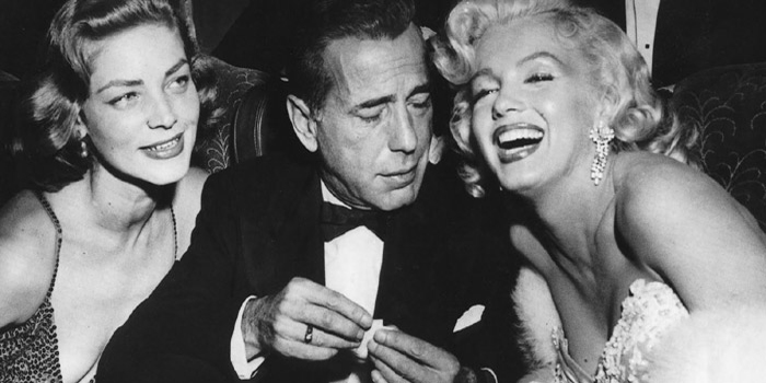Humphrey Bogart (1899-1957) with Marilyn Monroe (1926-1962) and Lauren Bacall (1924-).