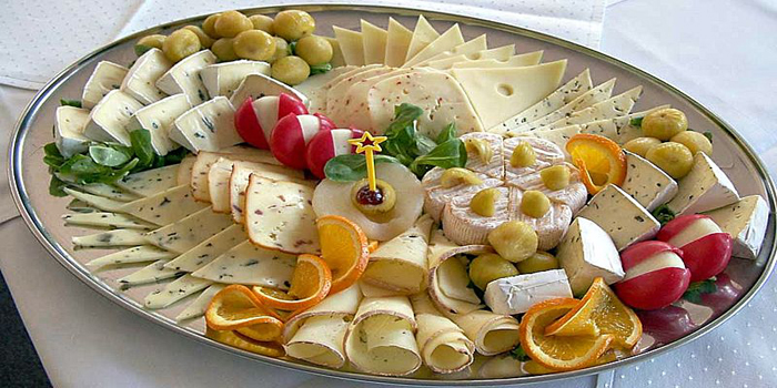 A platter with cheese and garnishes.