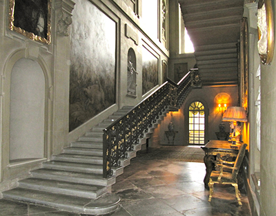 Easton Neston main staircase, with its wrought iron balustrade in the style of Jean Tijou, comprises two long, shallow flights ascending to the first floor gallery which is decorated with grisailles painted by Sir James Thornhill.